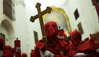 "A hooded penitent from ""Cristo de los Angeles"" brotherhood holds a cross inside the ""Gaitanas"" church before taking part in a traditional annual Holy Week procession in Toledo, Spain, Tuesday, April 11, 2017. Hundreds of processions take place throughout Spain during the Easter Holy Week. (AP Photo/Francisco Seco)"