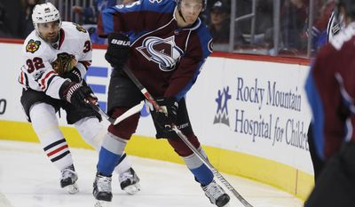 Colorado Avalanche center Mikhail Grigorenko, front, looks to pass the puck as Chicago Blackhawks defenseman Michal Rozsival, of the Czech Republic, covers in the third period overtime of an NHL hockey game Tuesday, April 4, 2017, in Denver. The Avalanche won 4-3 in overtime. (AP Photo/David Zalubowski)