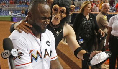 Wearing a monkey mask, Miami Marlins' Miguel Rojas hits Marcell Ozuna with a cream pie as he is interviewed on the field after the Marlins defeated the Atlanta Braves 8-4 in a baseball game, Tuesday, April 11, 2017, in Miami. Ozuna homered twice and had a career-high six RBIs to help Miami win its home opener against the Braves. (AP Photo/Wilfredo Lee)