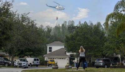 Suncoast Lakes resident Kristin Werner uses her cellphone to record a Florida Forest Service helicopter dropping water behind homes on the Silver Palm fire Tuesday, April 11, 2017, in Land O' Lakes. The Silver Palm Fire burned close to homes in the Suncoast Lakes subdivision Tuesday forcing residents to use garden hoses on vegetation and roofs around their property. (Chris Urso/The Tampa Bay Times via AP)