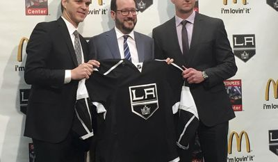 Los Angeles Kings president Luc Robitaille, left, holds up a team jersey with Anschutz Entertainment Group CEO Dan Beckerman, middle, and Kings general manager Rob Blake after a news conference Tuesday, April 11, 2017, in Los Angeles, Calif. Robitaille and Blake were promoted by the Kings after the firing of general manager Dean Lombardi and coach Darryl Sutter. (AP Photo/Greg Beacham)