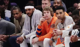 New York Knicks' Carmelo Anthony, second from left, watches his team play with teammates Lance Thomas, left, Kristaps Porzingis, center above, Kyle O'Quinn, Ron Baker, second from right, and Courtney Lee right, during the first half of an NBA basketball game against the Philadelphia 76ers, Wednesday, April 12, 2017, in New York. (AP Photo/Frank Franklin II)