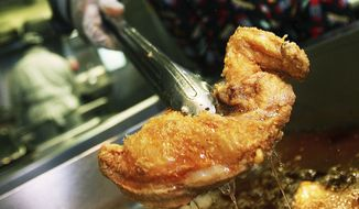 In this Friday, Sept. 29, 2006 file photo, H. Kenneth Woods, chef and owner of Sylvia's restaurant, cooks southern fried chicken using a soy bean oil that doesn't contain trans fats in New York's Harlem neighborhood. A study released Wednesday, April 12, 2017, suggests restrictions on heart-damaging fats in restaurant food may have helped prevent heart attacks in several New York counties. (AP Photo/Dima Gavrysh)