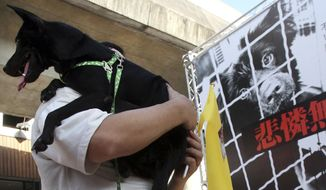 In this Sept. 17, 2011 file photo, a Taiwanese man holds his dog during a gathering to demand establishment of a government department to protect dogs and cats from their owners who abused or dumped the animals in Taipei, Taiwan. Taiwan on Wednesday, April 12, 2017 has banned the sale and consumption of dog and cat meat and increased the penalty for animal cruelty. (AP Photo/Chiang Ying-ying, file) **FILE**