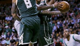 Boston Celtics guard Isaiah Thomas threads between Milwaukee Bucks guard Matthew Dellavedova (8) and center Greg Monroe, rear, on a drive to the basket during the first quarter of an NBA basketball game in Boston, Wednesday, April 12, 2017. (AP Photo/Charles Krupa)