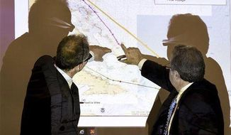 FILE - In this Thursday, Feb. 18, 2016 file photo, Charles Baird, former second mate of the El Faro, left, and Mike Kucharski with the National Transportation Safety Board discuss route options available to the El Faro when dealing with the approaching hurricane during a hearing investigating the ship's sinking in October 2015 in Jacksonville, Fla. Before the freighter El Faro sank, the captain was warned by a text message from his vacationing second mate that a storm looming offshore was forecast to become a hurricane, according to testimony given by Baird Thursday. (Bob Self/The Florida Times-Union via AP)