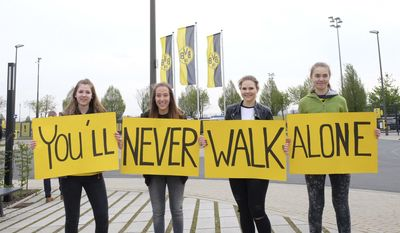 """Dortmund supporters hold posters """"You'll never walk alone"""" outside the training ground of Borussia Dortmund in Dortmund, Germany, Wednesday, April 12, 2017, one day after an explosion at the bus of the team prior to the Champions League quarterfinal soccer match between Borussia Dortmund and AS Monaco (AP Photo/Mike Corder)"""