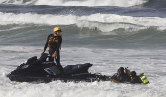 In this Monday, April 10, 2017, photo, a lifeguard in a watercraft tow two lifeguard divers back to shore after they completed a section in their search of the ocean floor for the body of a teenage boy from El Cajon, Calif., who went missing Sunday after being caught in a rip current in San Diego, Calif. The 17-year-old boy adjusting to a new life as a refugee in the United States after fleeing war-torn Syria with his parents and four sisters is presumed dead after disappearing in the ocean on his first trip to the beach. (John Gibbins/The San Diego Union-Tribune via AP)