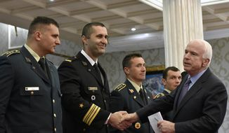 U.S. Sen. John McCain, right, shakes hand with Montenegrin army officers in Podgorica, Montenegro, Wednesday, April 12, 2017. McCain has congratulated Montenegro for its upcoming NATO membership, blasting Russia for its attempts to interfere in the Balkans. (AP Photo/Risto Bozovic)