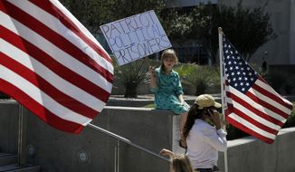 Nine-year-old Paylynn Lawrimore holds up a sign in support of defendants on trial in federal court, Wednesday, April 12, 2017, in Las Vegas. A federal jury in Las Vegas heard closing arguments in the trial of six men accused of wielding weapons to stop federal agents from rounding up cattle near Nevada rancher Cliven Bundy's property in 2014. (AP Photo/John Locher)