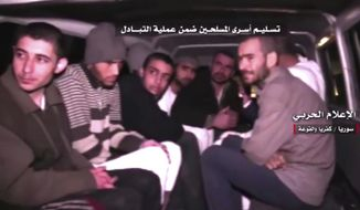 "This frame grab from video provided by the government-controlled Syrian Central Military Media, shows Syrian rebels sitting inside a vehicle of the Syrian Arab Red Crescent after they were released as part of a deal to evacuate over 10,000 residents from Madaya and Zabadani, two opposition-held areas near Damascus, and the two rebel-besieged villages of Foua and Kfarya, in Idlib province, northern Syria, Wednesday, April 12, 2017. Syria's government and rebels exchanged some 30 prisoners and nine bodies, part of a larger agreement to evacuate four besieged areas in different parts of the country, activists and officials said Wednesday. The Arabic words above read:""Handing over the fighter prisoners as part of the exchange deal."" (Syrian Central Military Media, via AP)"