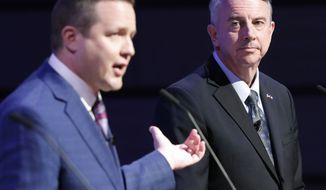 Republican gubernatorial candidate, Ed Gillespie, right, listens as Corey Stewart, left, gestures during a debate at Liberty University in Lynchburg, Va., Thursday, April 13, 2017. (AP Photo/Steve Helber)'