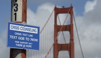 A suicide prevention sign is posted at the Golden Gate Bridge, Thursday, April 13, 2017, in San Francisco. Local officials gathered Thursday at the orange-red span to mark the beginning of work to line both sides of the bridge with steel netting. (Alan Dep/Marin Independent Journal via AP)