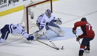 Toronto Maple Leafs goalie Frederik Andersen (31) makes a save in front of defenseman Morgan Rielly (44) and Washington Capitals right wing T.J. Oshie (77) during the third period in Game 1 of an NHL Stanley Cup first round playoff series in Washington, Thursday, April 13, 2017. (AP Photo/Molly Riley)