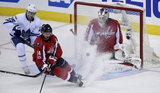 Washington Capitals goalie Braden Holtby (70) watches the puck as right wing Justin Williams (14) and Toronto Maple Leafs left wing James van Riemsdyk (25) skate for it during the third period in Game 1 of an NHL Stanley Cup first-round playoff series in Washington, Thursday, April 13, 2017. (AP Photo/Molly Riley)