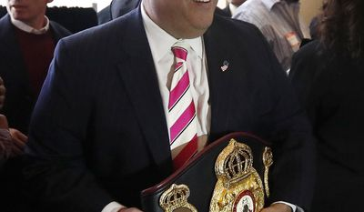 New Jersey Gov. Chris Christie poses for photographs with a belt presented to him by boxer Mike Tyson for Christie's work in promoting help for ex-prisoners re-entering society, during the 4th Annual New Jersey Prisoner Reentry Conference, Thursday, April 13, 2017, in Jersey City, N.J. (AP Photo/Julio Cortez)
