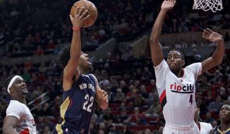 New Orleans Pelicans guard Quinn Cook, center, shoots between Portland Trail Blazers forwards Maurice Harkless, right, and Portland Trail Blazers Noah Vonleh, left, during the first half of an NBA basketball game in Portland, Ore., Wednesday, April 12, 2017. (AP Photo/Craig Mitchelldyer)