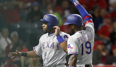 Texas Rangers' Jurickson Profar, right, congratulates Elvis Andrus, left, after scoring on an RBI double by Joey Gallo during the fifth inning of a baseball game against the Los Angeles Angels, Wednesday, April 12, 2017, in Anaheim, Calif. (AP Photo/Ryan Kang)