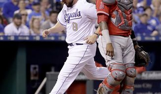 Kansas City Royals' Mike Moustakas, left, crosses the plate past Los Angeles Angels catcher Martin Maldonado to score on a ground-out by Eric Hosmer during the third inning of a baseball game Friday, April 14, 2017, in Kansas City, Mo. (AP Photo/Charlie Riedel)