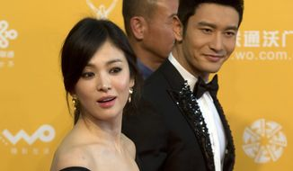 FILE - In this April 16, 2016 file photo, South Korean actress Kim Hye-Kyo, front, walks with Chinese actor Huang Xiaoming, right, as they arrive for the 4th Beijing International Film Festival held in Beijing, China. An organizer of the Beijing International Film Festival has denied that politics had anything to do with this year's lack of South Korean participants. South Korea's Yonhap news agency last month cited unidentified Korean industry sources as saying that invitations for some Korean films to screen during the April 16-23 festival had been revoked. However, Ai Dongyun, vice secretary of the festival organizing committee, said Friday, April 14, 2017, that films were chosen on merit and without consideration for national origin. (AP Photo/Ng Han Guan, File)