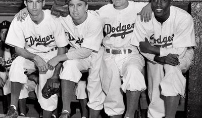 FILE - In this April 15, 1947, file photo, from left, Brooklyn Dodgers baseball players John Jorgensen, Pee Wee Reese, Ed Stanky and Jackie Robinson pose at Ebbets Field in New York. The first statue in Dodger Stadium history belongs to Jackie Robinson. The team will unveil his likeness during Jackie Robinson Day festivities on Saturday, April 15, 2017, with his wife and extended family in attendance on the 70th anniversary of him breaking baseball's color barrier (AP Photo, File)