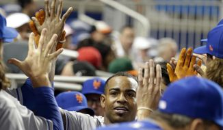 New York Mets' Yoenis Cespedes is congratulated in the dugout after hitting a home run during the third inning of the team's baseball game against the Miami Marlins, Thursday, April 13, 2017, in Miami. (AP Photo/Lynne Sladky)