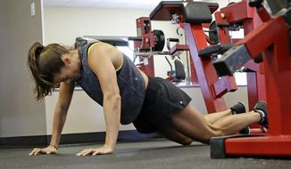 In this Saturday, Feb. 18, 2017 photo, Danica Patrick works out at Daytona International Speedway, in Daytona Beach, Fla. With Danica Patrick's auto racing career possibly nearing an end in the not-too-distant future, what might have seemed like an off-track hobby in the health and fitness world is being fast-tracked into something far bigger. (AP Photo/John Raoux)