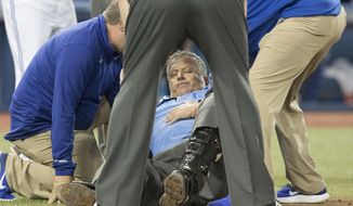 Home plate umpire Dale Scott is attended to on the field in the eighth inning after he was hit by a foul tip during a baseball game between the Toronto Blue Jays and the Baltimore Orioles in Toronto on Friday April 14, 2017. (Fred Thornhill/The Canadian Press via AP)