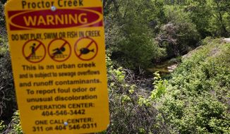 A signs warns against swimming and fishing along a section of Proctor Creek in Atlanta, Thursday, April 13, 2017. Growing up, Mark Teixeira loved playing at a park near his home. Now, he's trying to bring those same opportunities to an impoverished area in his second home. Hopefully the retired baseball star will lead others to become eco-athletes, lending their considerable influence and financial power to one of the world's most pressing issues: preserving the environment. (AP Photo/David Goldman)