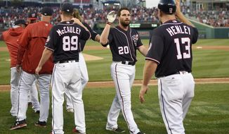 Washington Nationals' Daniel Murphy (20) celebrates with third base coach Bob Henley (13) after the team's baseball game against the Philadelphia Phillies, Friday, April 14, 2017, in Washington. The Nationals won 3-2 in 10 innings. (AP Photo/Nick Wass)