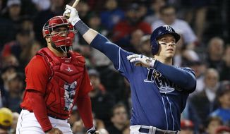 Tampa Bay Rays' Logan Morrison, right, watches his grand slam in front of Boston Red Sox's Sandy Leon during the third inning of a baseball game in Boston, Friday, April 14, 2017. (AP Photo/Michael Dwyer)