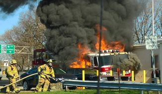 In this image taken from video, flames engulf a firetruck near the toll booth at Exit 36 on Interstate 90, in Salina, N.Y., Friday, April 14, 2017. Fire officials tell WSTM-TV that the vehicle was an old truck from the Kansas City Fire Department that was being driven to a fire department in Canada. The driver escaped without injury. (Spectrum News Syracuse via AP)