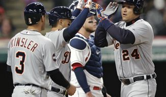 Detroit Tigers' Miguel Cabrera, right, is congratulated by Jose Iglesias, center, and Ian Kinsler after Cabrera hit a three-run home run off Cleveland Indians starting pitcher Trevor Bauer during the fifth inning of a baseball game, Friday, April 14, 2017, in Cleveland. Kinsler and Iglesias scored on the homer. (AP Photo/Tony Dejak)