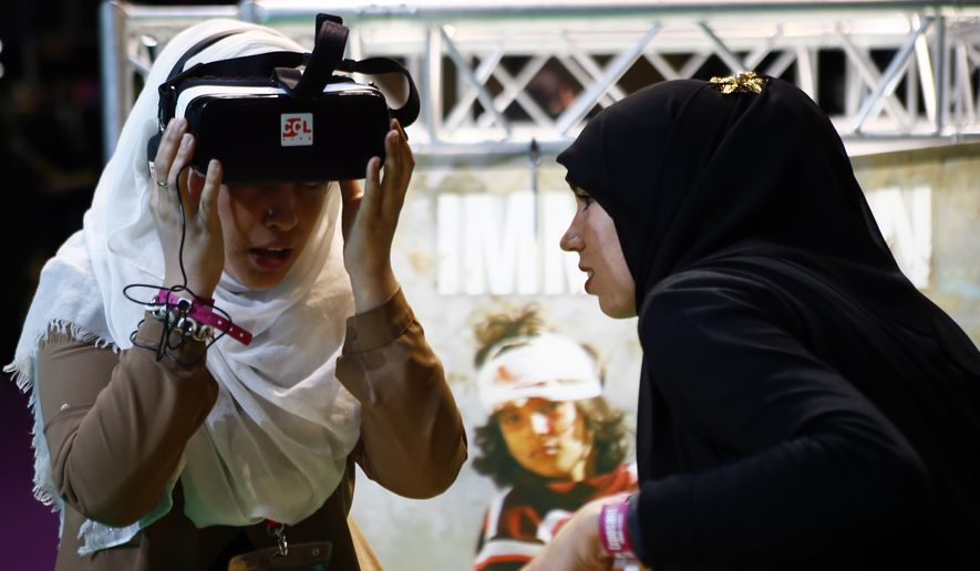 Women look at video of Syria Charity presentation inside an exhibition hall at the France Muslim Annual Fair in Le Bourget, north of Paris, in this Saturday, April 15, 2017, file photo. Tens of thousands of Muslims are expected at the three-day event this weekend organized by the ultra-conservative Union of Islamic Organizations of France. It includes merchant stalls, Koran readings, prayers and speeches by leading Muslim figures as Muslims of France want to make sure their voices are heard in France's presidential elections. (AP Photo/Francois Mori)