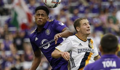 Orlando City's Cristian Higuita (7) and Los Angeles Galaxy's Nathan Smith, right, try to move the ball to a teammate on a header during the second half of an MLS soccer game, Saturday, April 15, 2017, in Orlando, Fla. (AP Photo/John Raoux)