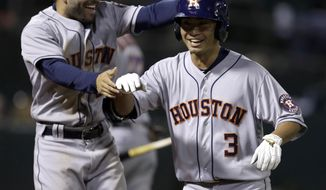 Houston Astros Norichika Aoki (3) celebrates with Jose Altuve, left, after hitting a home run off Oakland Athletics' Kendall Graveman during the fifth inning of a baseball game Friday, April 14, 2017, in Oakland, Calif. (AP Photo/Ben Margot)