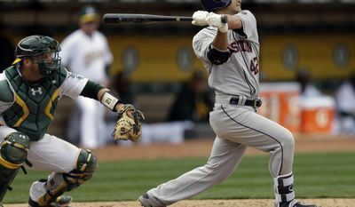 Houston Astros Norichika Aoki, right, swings for an RBI-sacrifice fly off Oakland Athletics' Sean Doolittle in the eighth inning of a baseball game Saturday, April 15, 2017, in Oakland, Calif. (AP Photo/Ben Margot)