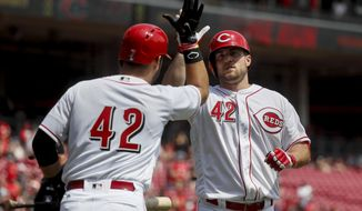 Cincinnati Reds' Scott Schebler, right, celebrates with Eugenio Suarez, left, after hitting a solo home run off Milwaukee Brewers starting pitcher Zach Davies in the second inning of a baseball game, Saturday, April 15, 2017, in Cincinnati. (AP Photo/John Minchillo)