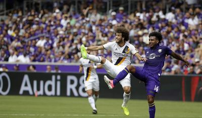 Los Angeles Galaxy's Joao Pedro, left, clears the ball away from Orlando City's Giles Barnes (14) during the first half of an MLS soccer game, Saturday, April 15, 2017, in Orlando, Fla. (AP Photo/John Raoux)