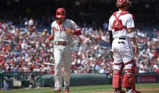 Philadelphia Phillies second baseman Cesar Hernandez, left, comes home to score as Washington Nationals catcher Jose Lobaton, right, looks on during the fourth inning of a baseball game, Saturday, April 15, 2017, in Washington. (AP Photo/Nick Wass)