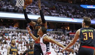 Atlanta Hawks center Dwight Howard, back center, and Washington Wizards forward Otto Porter Jr., front center, battle for a rebound during the first half in Game 1 of a first-round NBA basketball playoff series, in Washington, Sunday, April 16, 2017. The Wizards won 114-107. (AP Photo/Manuel Balce Ceneta)
