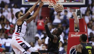 Washington Wizards forward Markieff Morris (5) dunks the ball while Atlanta Hawks forward Paul Millsap (4) and Dwight Howard (8) watch during the second half in Game 1 of a first-round NBA basketball playoff series, in Washington, Sunday, April 16, 2017. The Wizards won 114-107. (AP Photo/Manuel Balce Ceneta)