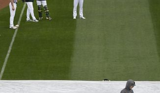 Oakland Athletics prepare for the baseball game against the Houston Astros as a groundskeeper walks on a tarp covering the infield on Sunday, April 16, 2017, in Oakland, Calif. (AP Photo/Ben Margot)