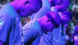Boston Celtics' Isaiah Thomas, center, and teammates bow their heads during a moment of silence for Thomas' sister Chyna before a first-round NBA playoff basketball game against the Chicago Bulls Sunday, April 16, 2017, in Boston. (AP Photo/Michael Dwyer)