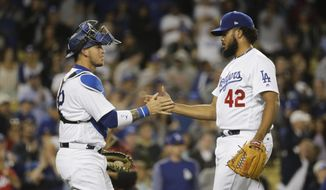 Los Angeles Dodgers relief pitcher Kenley Jansen, right, and catcher Yasmani Grandal shake hands as they celebrate the team's 8-4 win against the Arizona Diamondbacks in a baseball game, Saturday, April 15, 2017, in Los Angeles. (AP Photo/Jae C. Hong)