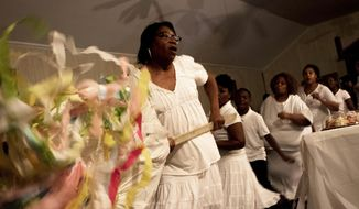 In this Saturday, April 15, 2017, photo, Hattie Addison Burkhalter carries the banner during the Easter Rock at Original True Light Baptist Church in Winnsboro, La. The public was invited to attend the annual Easter vigil ceremony, Rocking to a Risen Savior, at the old plantation church Saturday. (Hannah Baldwin/The News-Star via AP)