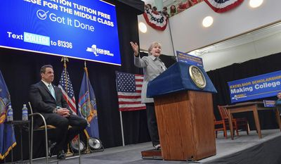 """FILE - In this April 12, 2017, file photo, provided by the Office of Governor Andrew M. Cuomo, Hillary Clinton addresses the audience as New York Gov. Andrew Cuomo listens at LaGuardia Community College in the Queens borough of New York, where Clinton joined Cuomo for a ceremonial signing of the state's new free tuition bill. It's the hope of proponents such as Bernie Sanders and Clinton, who made debt-free college a key talking point in their Democratic presidential campaigns, that New York's first-in-the-nation free tuition program for middle-class students will spread to other states. And that's the prediction of Cuomo, its main champion, who called the plan a """"model for the nation."""" (Darren McGee/Office of Governor Andrew M. Cuomo via AP, File)"""