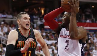 Washington Wizards guard John Wall, right, looks for a receiver while Atlanta Hawks forward Mike Muscala, left, defends during the first half in Game 1 of a first-round NBA basketball playoff series, in Washington, Sunday, April 16, 2017. (AP Photo/Manuel Balce Ceneta)