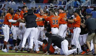 Miami Marlins players surround J.T. Riddle after he hit a two-run home run during the ninth inning of a baseball game against the New York Mets, Sunday, April 16, 2017, in Miami. The Marlins defeated the Mets 4-2. (AP Photo/Wilfredo Lee)