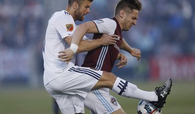 Real Salt Lake defender Chris Wingert, left, fights for control of the ball with Colorado Rapids forward Kevin Doyle in the first half of an MLS soccer match, Saturday, April 15, 2017, in Commerce City, Colo. (AP Photo/David Zalubowski)